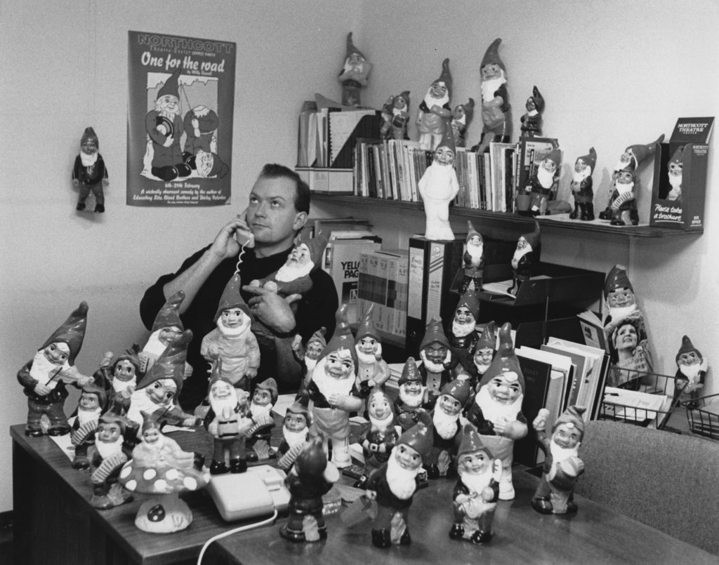 John Durnin in his office surrounded by dozens of garden gnomes arranged on the desk