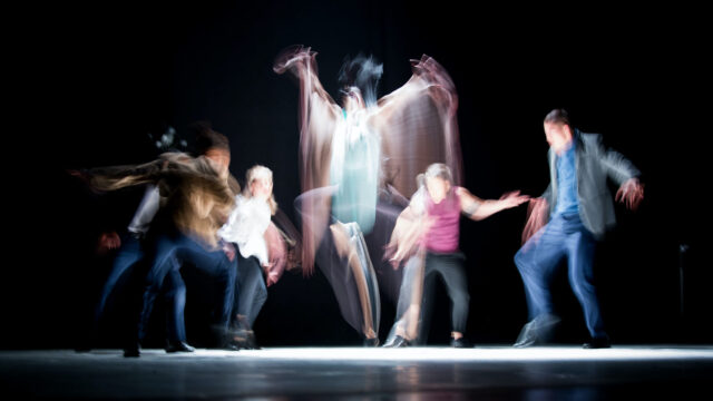 Long exposure photo of performers moving on stage