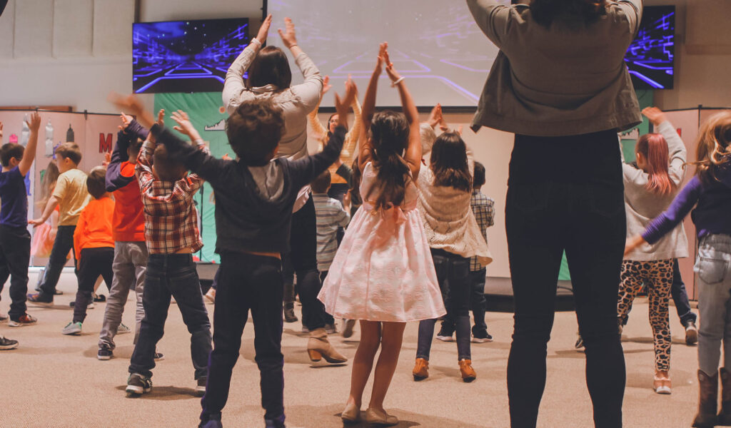 A large group of children and three adults clapping their hands above their head in unison