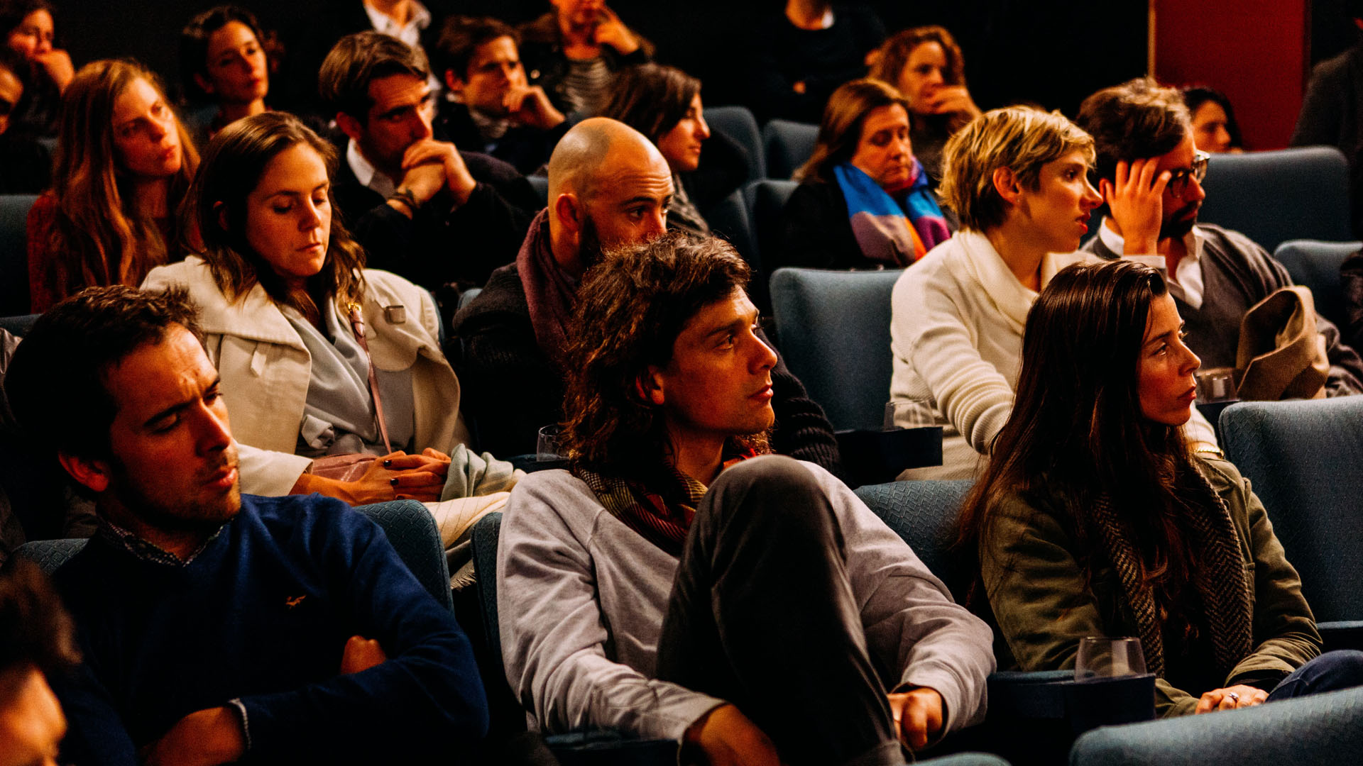 Photograph of several people sat in audience seats watching something