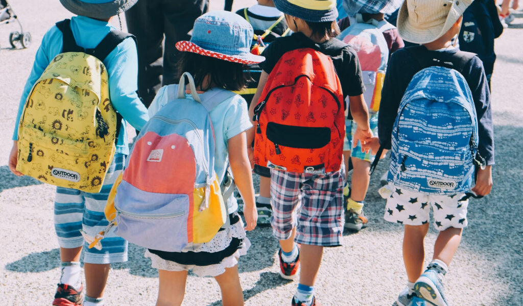 Photo of a group of children outdoors wearing colourful rucksacks and hats