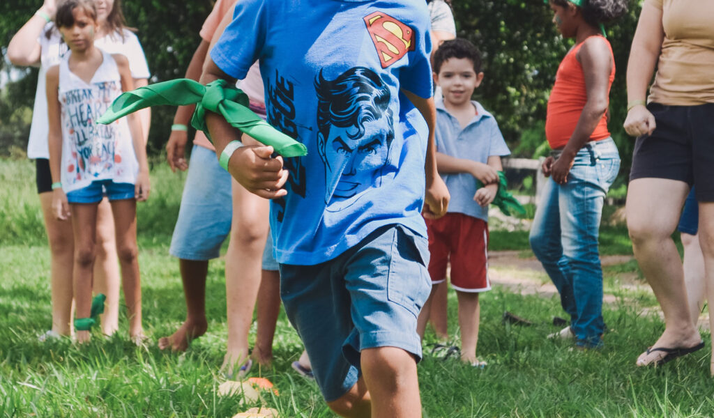 Photo of a group of children; the child in the foreground wears a Superman t-shirt and has a green neckscarf tied around their arm