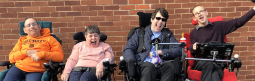 Photo of four adults in mobility chairs, all smiling