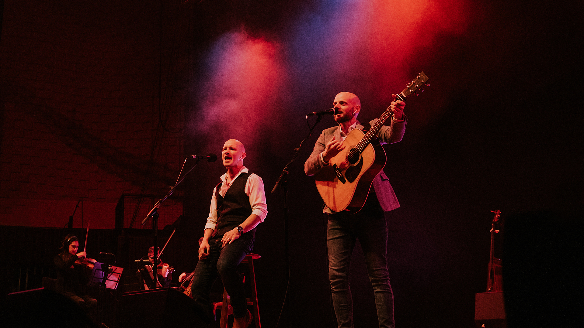 Two men performing Simon and Garfunkel songs on stage, one holding a guitar, with a string trio in the background