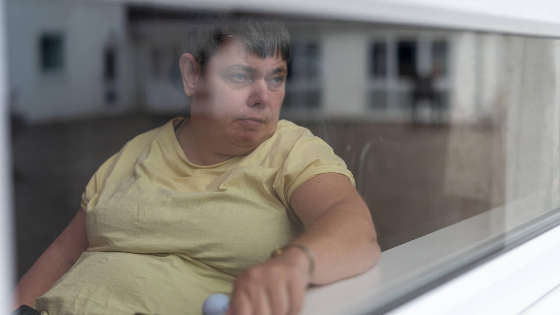 A woman in a wheelchair, looking out at the world through the window