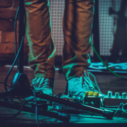 A photo of someone's feet surrounded by cables and switches backstage