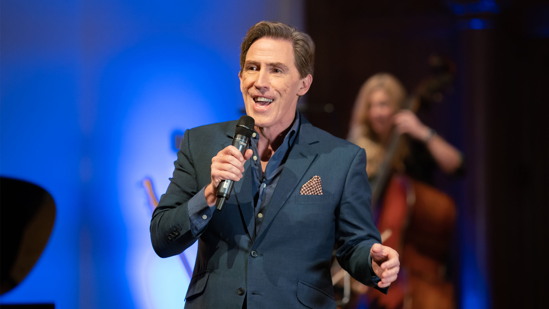 Production image of Rob Brydon on stage - smiling wide, microphone in hand