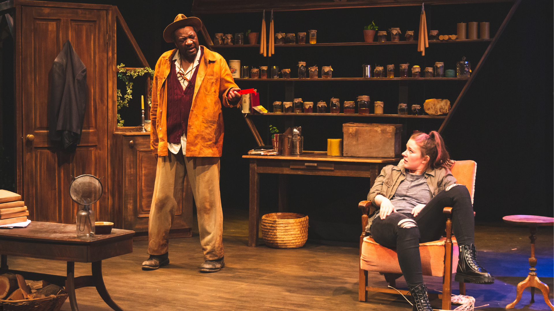The Honey Man Production Photo: Inside Honey Man's house, Misty (Amy Kennedy) sits in an armchair, her leg slung over the arm rest, as Honey Man (Everal Walsh) stands next to her