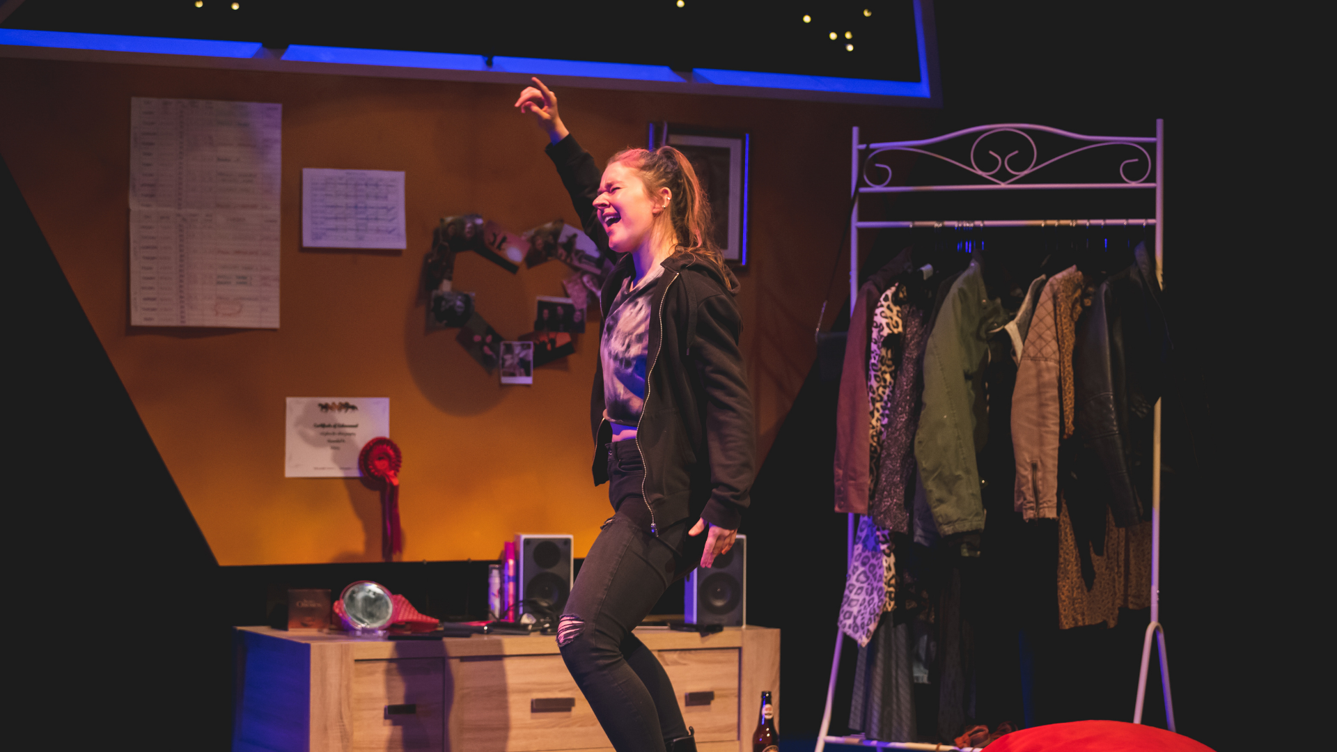 The Honey Man Production Photo: Misty (Amy Kennedy) dances in her bedroom, surrounded by clothes, fairy-lights and dressed in gothy black clothing