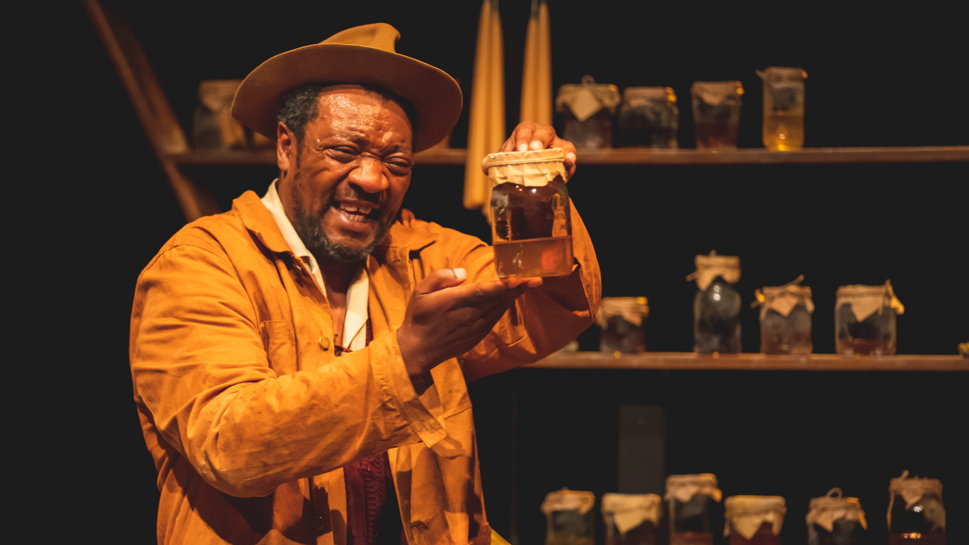 The Honey Man Production Photo: Honey Man (Everal Walsh) holds up a jar of honey while smiling