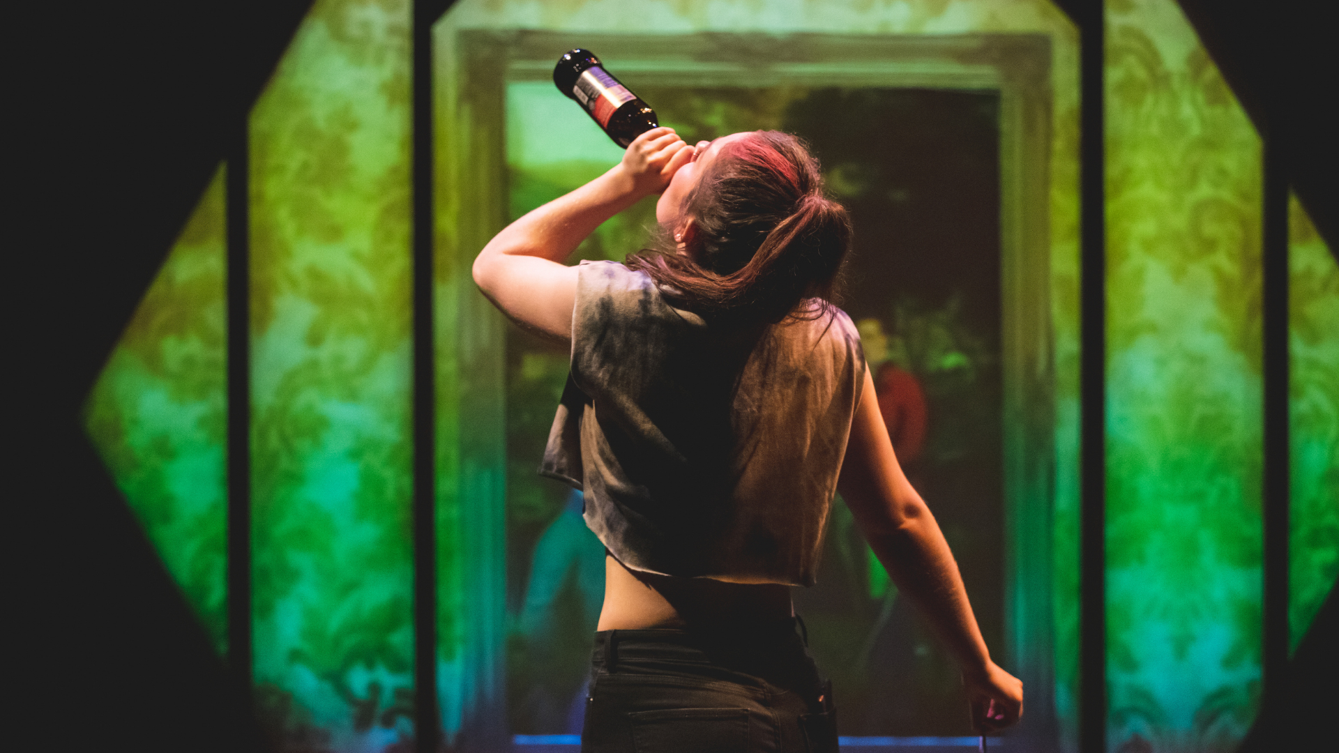 The Honey Man Production Photo: Misty (Amy Kennedy) dances and takes a swig from a bottle of beer, backlit by a colourful projection