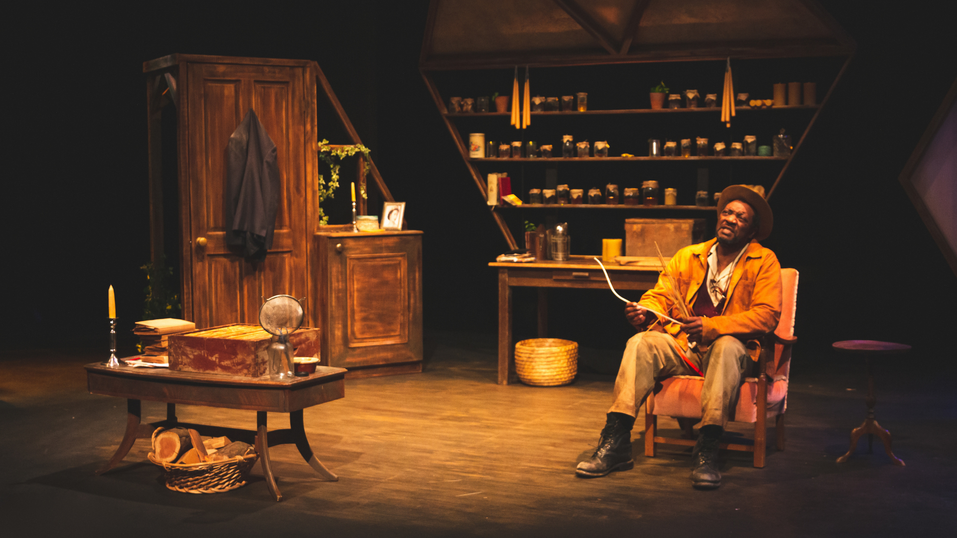 The Honey Man Production Photo: Honey Man (Everal Walsh) sits in an armchair in his house, surrounded by bee keeping equipment and jars of honey