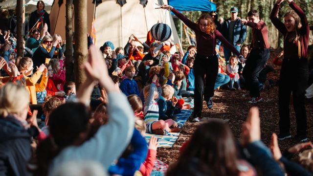 Paddleboat Theatre outside with a large group of children all around - lots of energy and colours