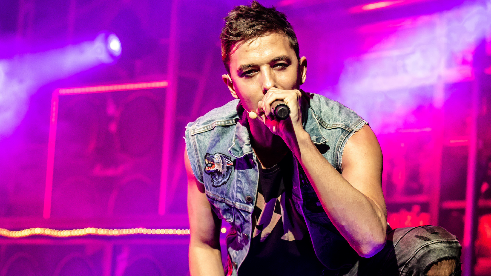 Rock of Ages production shot: the lead male actor looks directly into the camera as he holds a microphone and sings