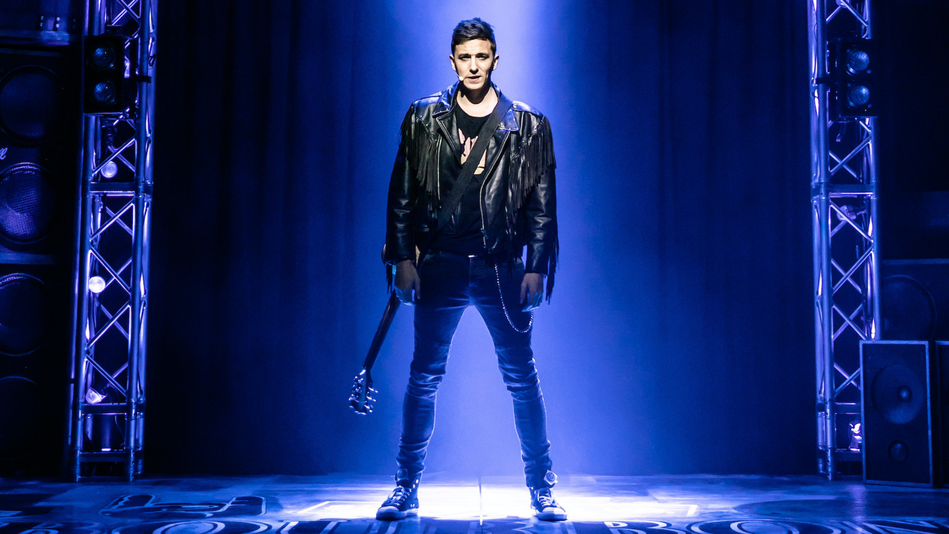 Rock of Ages production shot: the lead male actor stand alone on stage in a spotlight, carrying a guitar