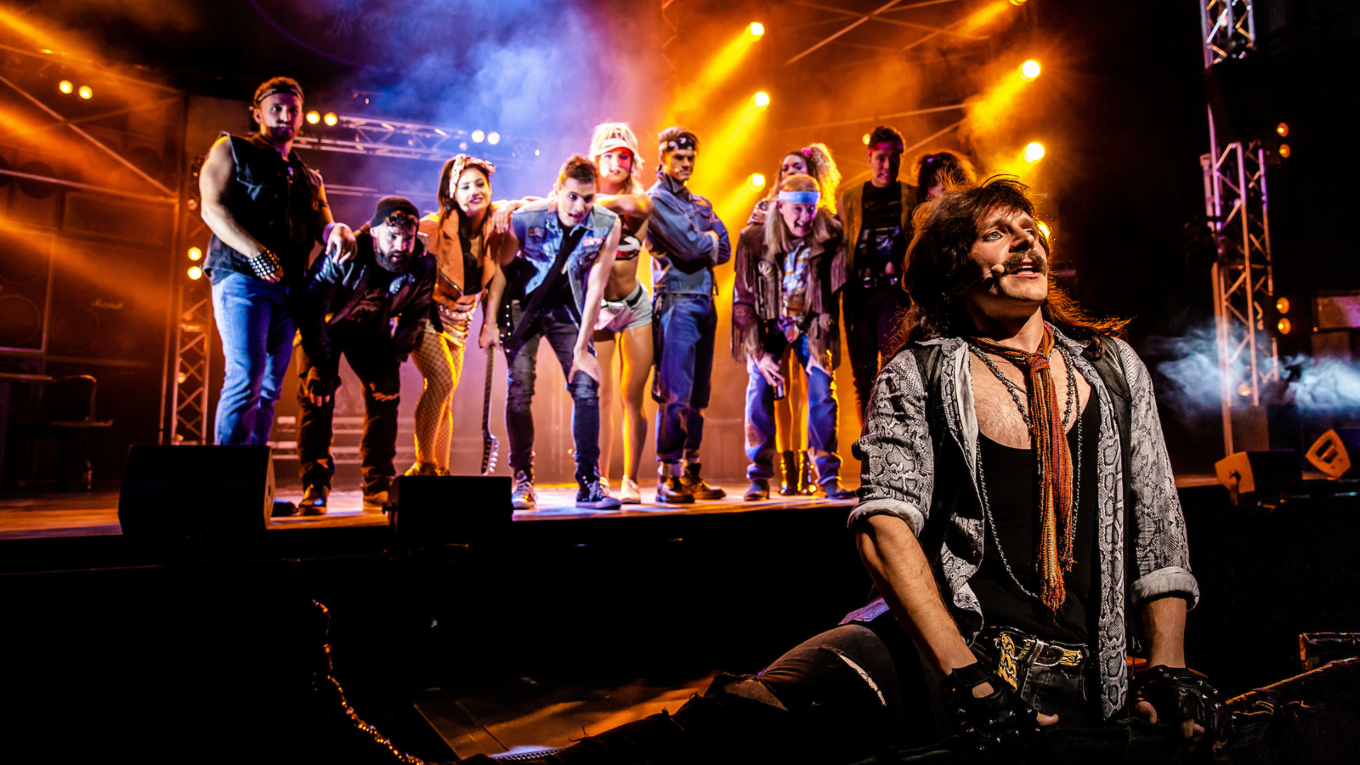 Rock of Ages production shot: a male actor sits on the edge of the stage, staring off into the audience, while the other cast members stand behind