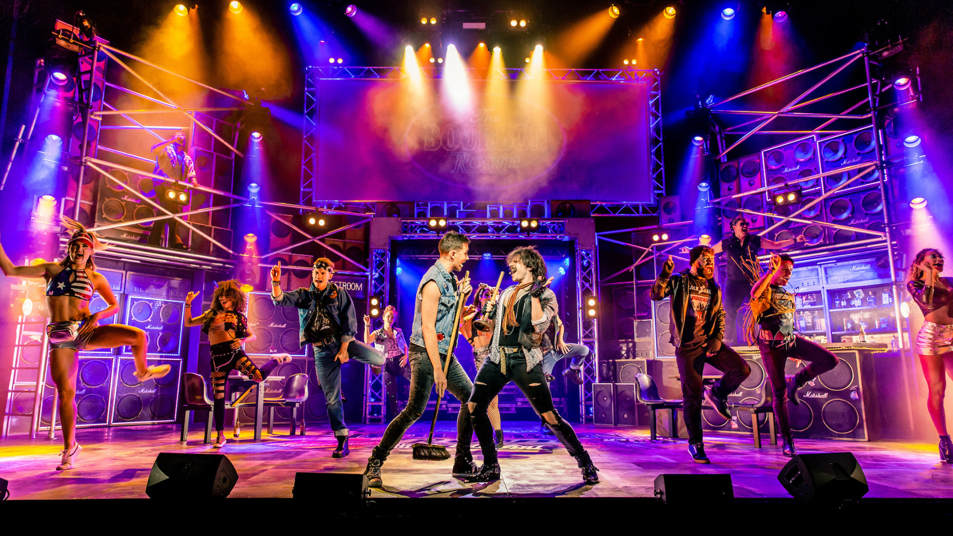 Rock of Ages 2018/19 tour production shot: Two male performers stand face to face, singing, while others dance in the background