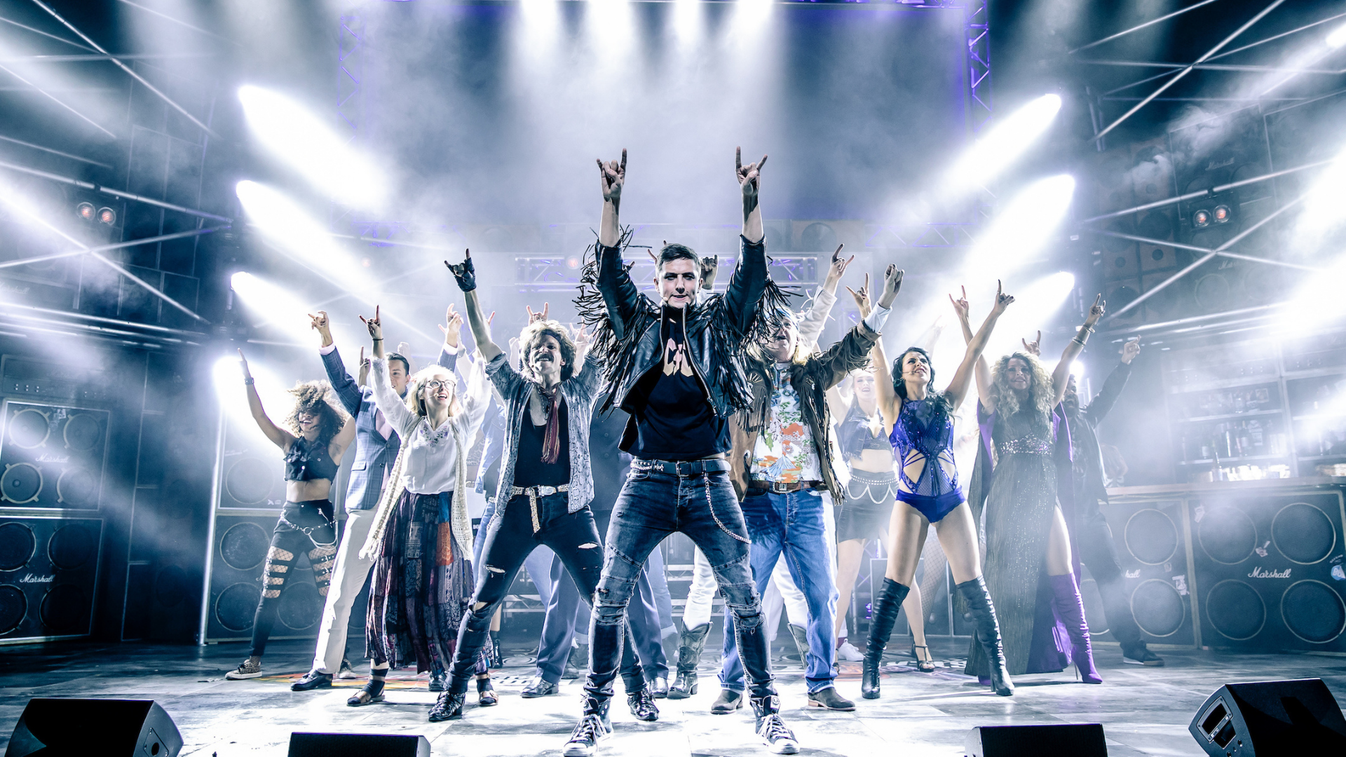Rock of Ages production shot: The cast stand under dramatic spotlights with their arms above their heads and their hands making the 'rock and roll' gesture'