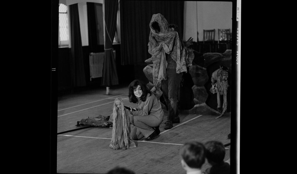 Black and white photo of performance in a school, an ominous hooded figure and a small puppet with long hair and long robes at the centre: The Celts and Their Stories 1971