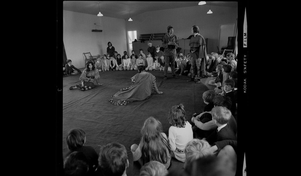 Black and white photo of performance in a school, children sitting on the floor watching: The Celts and Their Stories 1971