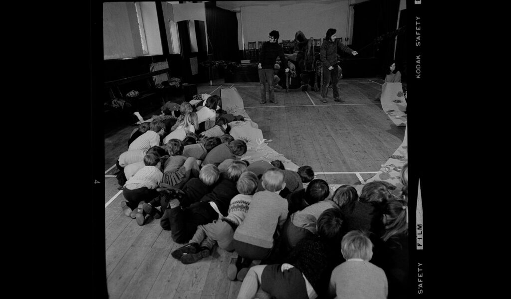 Black and white photo of performance in a school, children huddled around like they're hiding behind a set piece: The Dartmoor Project 1971