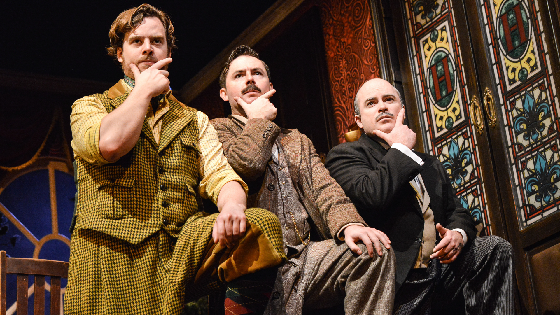 The Play That Goes Wrong Production Shot: Robert (Matthew Howell), Chris (James Watterson) and Dennis (Edward Howells) are standing next to each other all in the same position - one foot up on a rest, left hand resting on their left knee and their finger and thumb (right hand) stroking their chin.