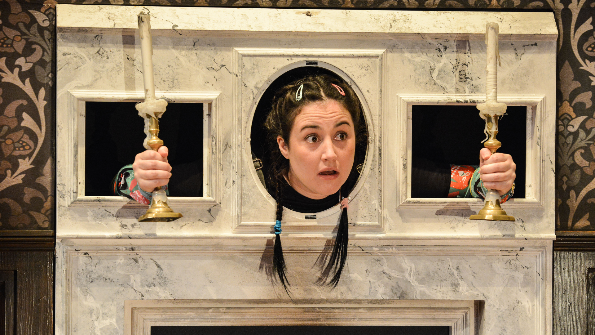 The Play That Goes Wrong Production Shot: A close up of Annie (Laura Kirman) who is stuck in a fireplace mantle piece, with her head through the middle hole and her arms through holes either side of her holding candlesticks.