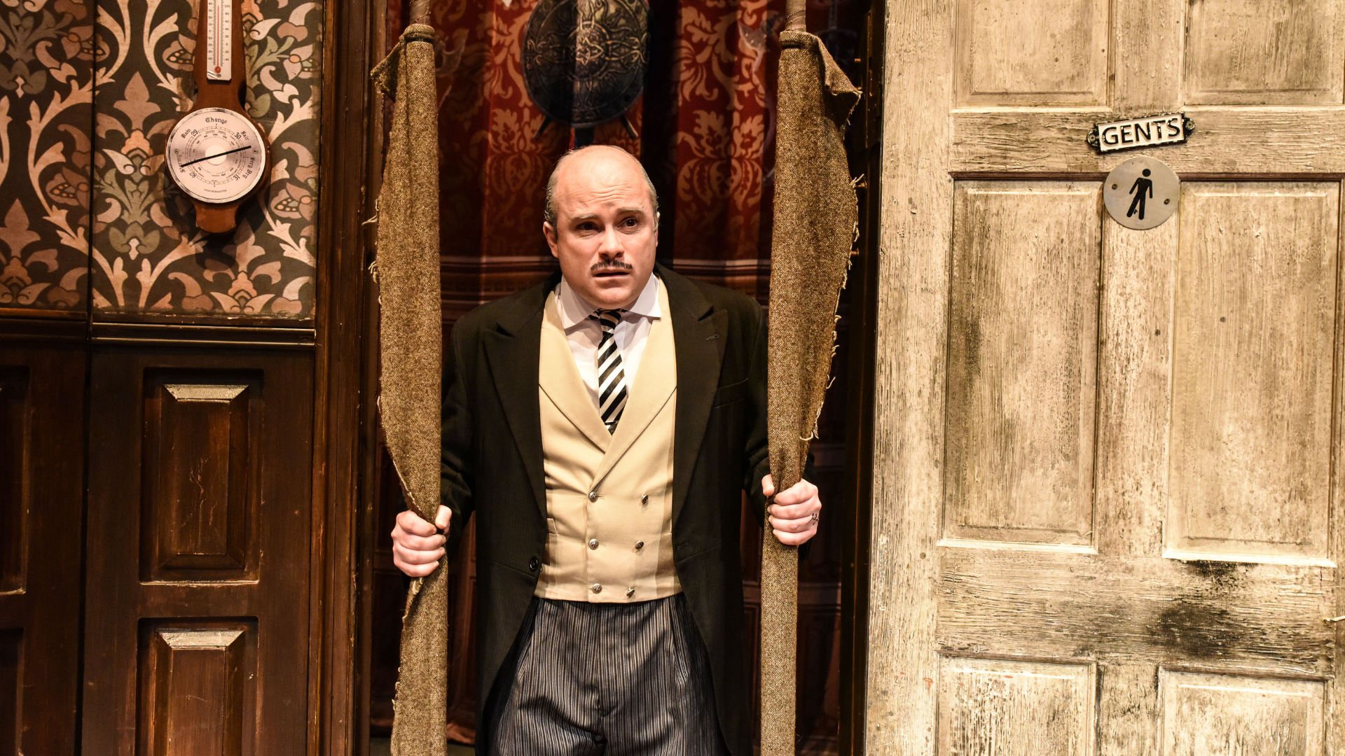 The Play That Goes Wrong Production Shot: A close up of Dennis (Edward Howells) who is holding 2 long rolls of fabric and is looking perplexed