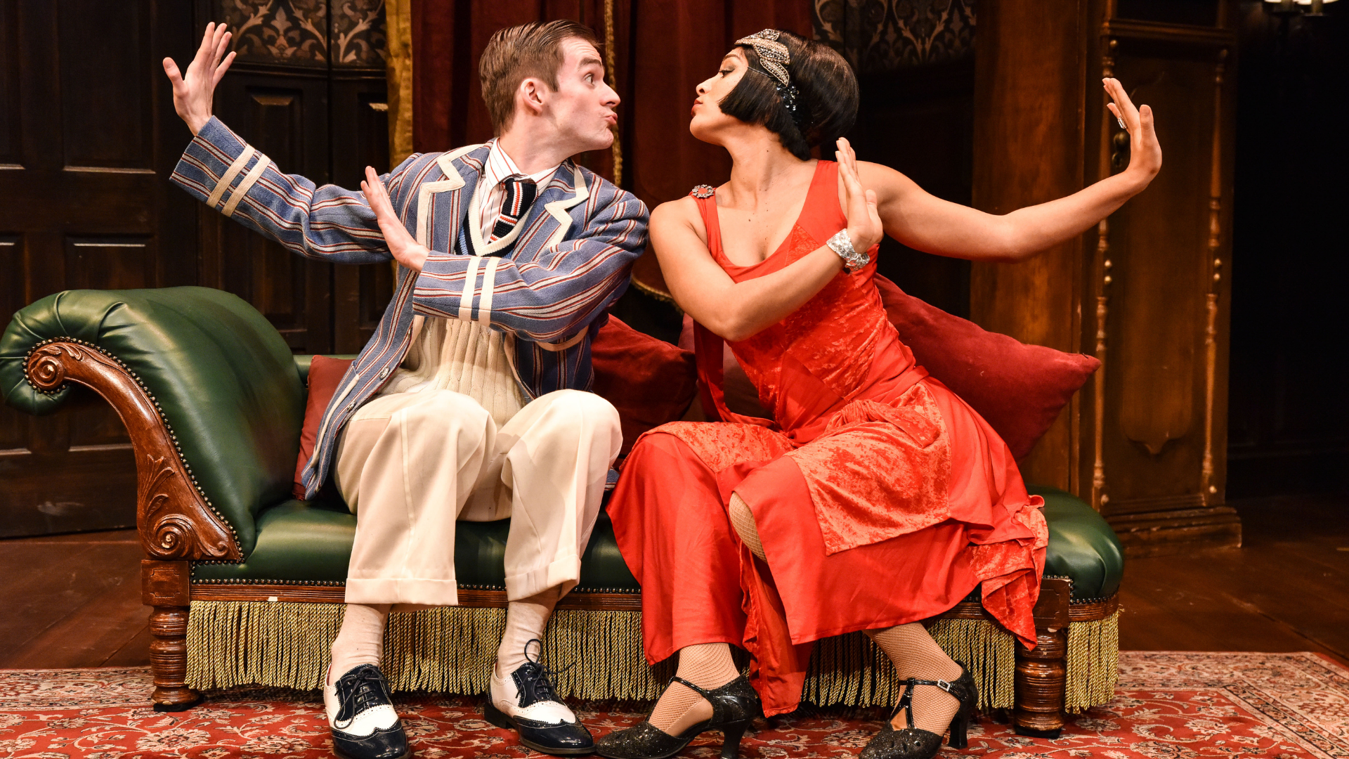 The Play That Goes Wrong Production Shot: Max (Tom Babbage) and Sandra (Laura White) are sat down on the chaise longue looking at each other pouting lips as if to kiss.