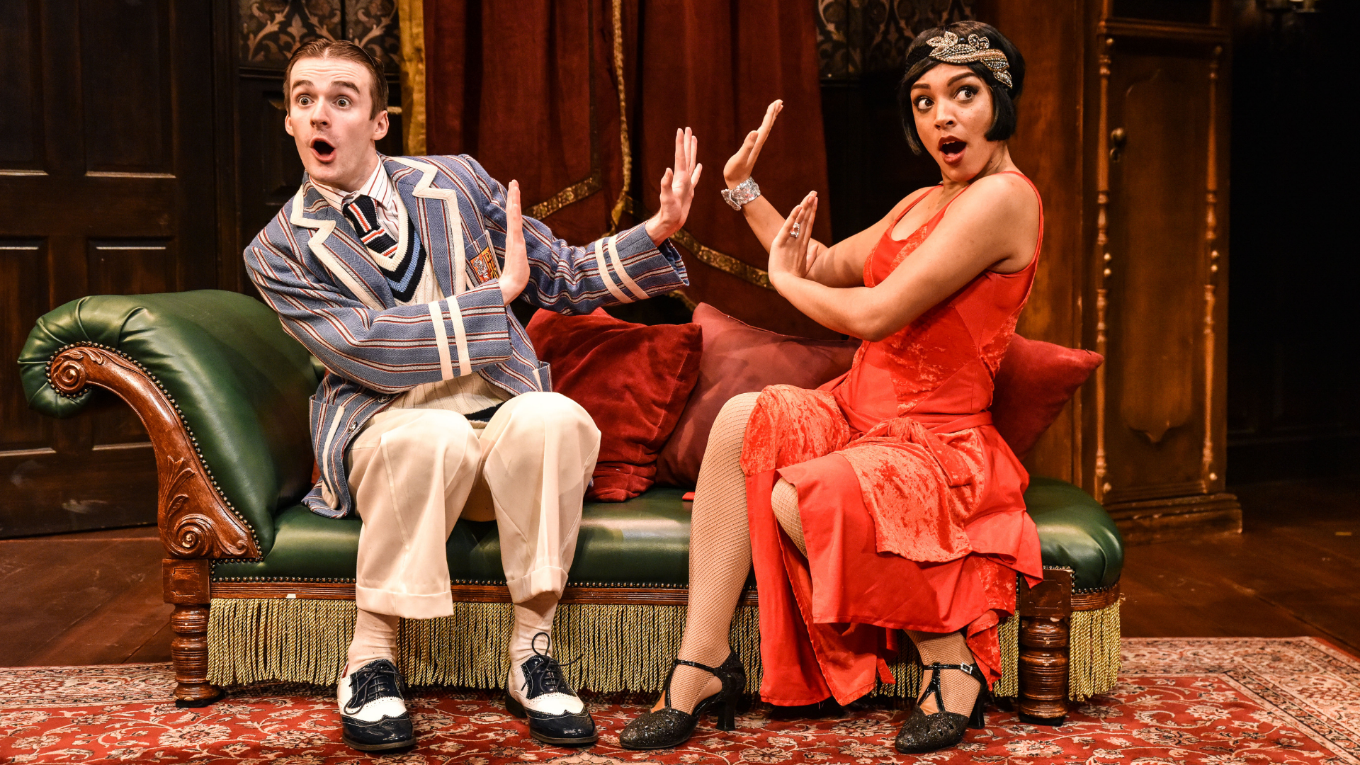 The Play That Goes Wrong Production Shot: Max (Tom Babbage) and Sandra (Laura White) are sat down on the chaise longue looking at the audience with a shocked face and their hands up as if they are pushing each other away.