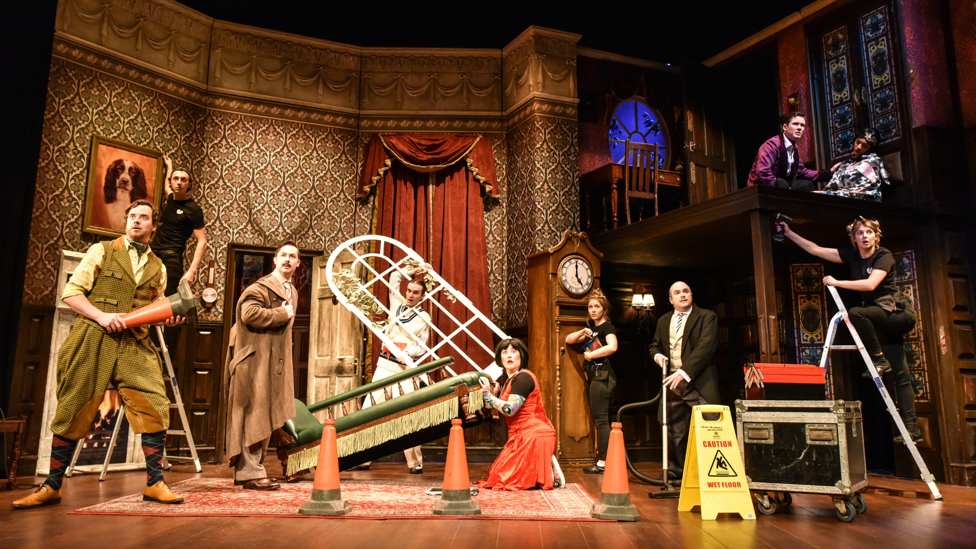The Play That Goes Wrong Production Shot: A wide shot of the main cast looking at the audience with shocked faces.