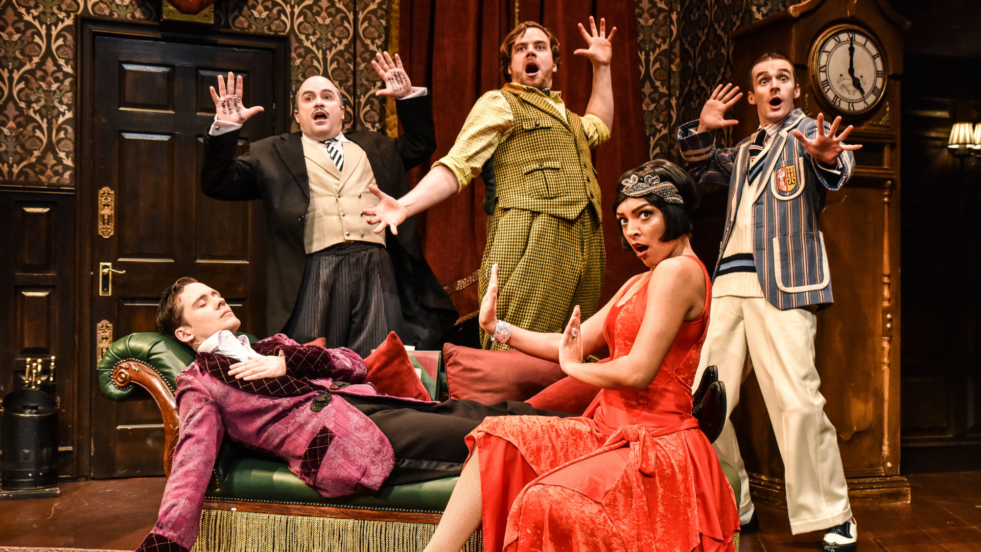 The Play That Goes Wrong Production Shot: Jonathan (Seán Carey) is laid down on a chaise longue with his eyes closed. He is surrounded by Dennis (Edward Howells), Robert (Matthew Howell), Sandra (Laura White) and Max (Tom Babbage) who all are looking towards the audience with shocked looks on their faces.