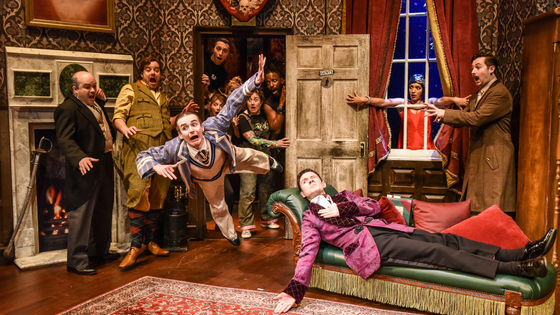 The Play That Goes Wrong Production Shot: Jonathan (Seán Carey) is laid down on a chaise longue with one eye open. Max (Tom Babbage) has burst into the scene falling through a door. Everyone else (9 cast members) are towards the back of the scene and looking scared as Max is falling.