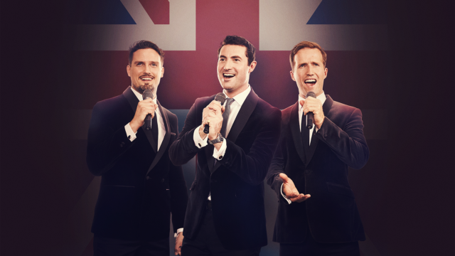 Three signers of Blake in drk suits, in front of a British flag
