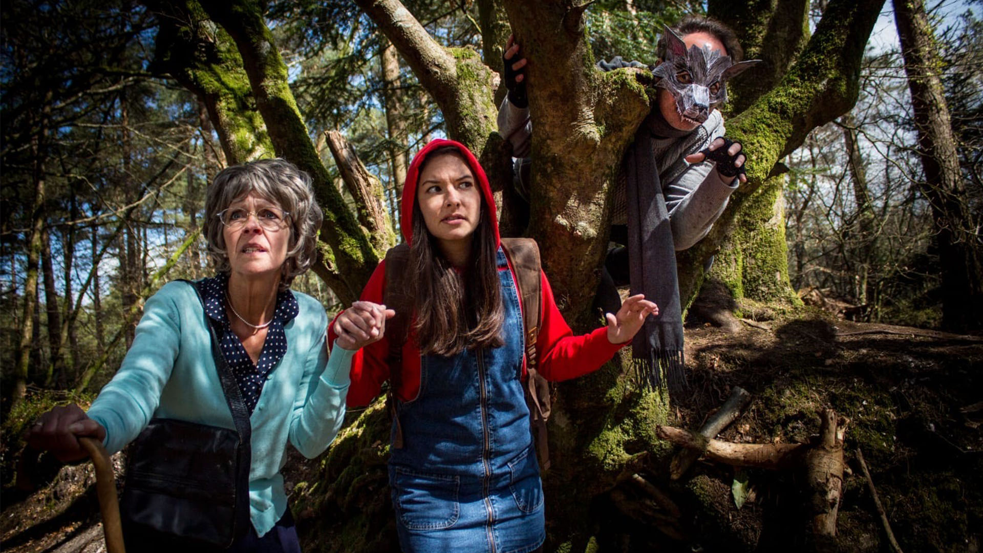 A modern Little Red Riding Hood and grandma are walking through the forest, concerned looks on their faces. A wolf is watching them from a tree right behind them, portrayed by an actor wearing grey clothing, a grey scarf, fingerless gloves and a very intricate and geometric wolf's mask