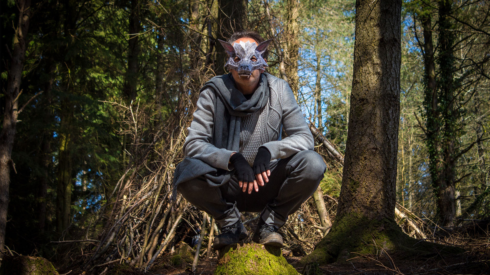 Little Red Riding Hood's Wolf is sitting crouched on a boulder in the woods,portrayed by an actor wearing grey clothing, a grey scarf, fingerless gloves and a very intricate and geometric wolf's mask