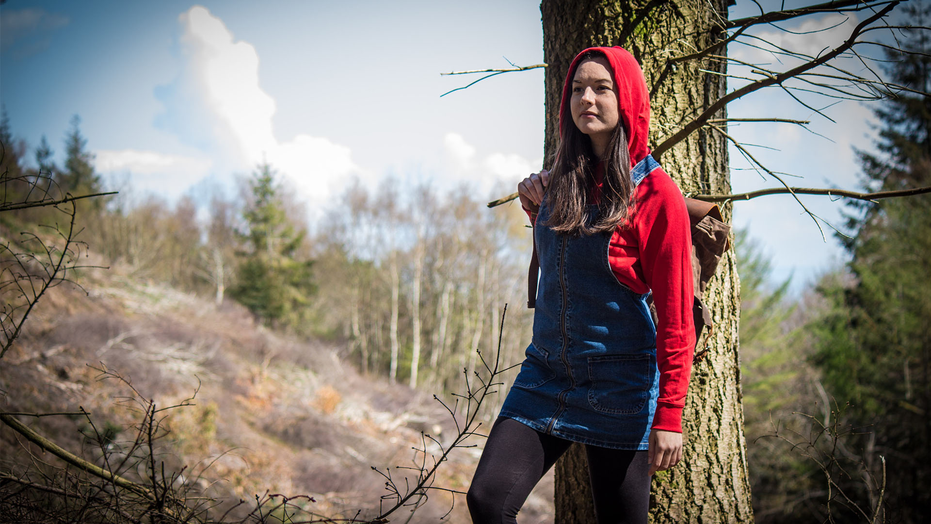 A modern-day Little Red Riding Hood is walking in the woods, wearing a blue jean overall dress with a red hoodie underneath, long brown hair peaking from under the hood. She's looking really determined.