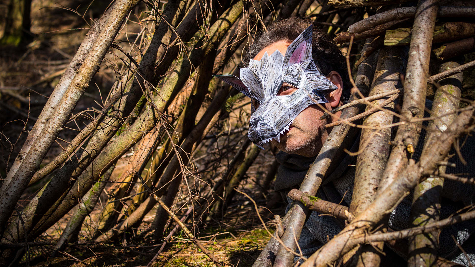The Big Bad Wolf hiding between branches, portrayed by an actor wearing grey clothing, a grey scarf, fingerless gloves and a very intricate and geometric wolf's mask