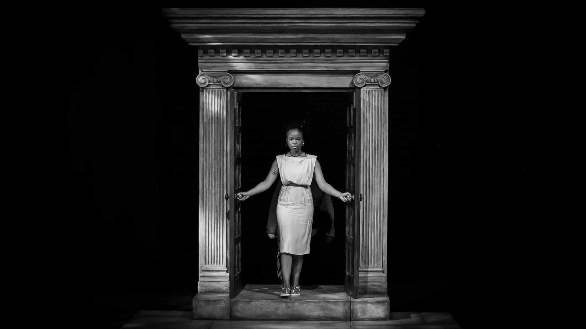 Antigone Rehearsals - Rachel Nwokoro as Antigone, defiantly walking through an ancient looking pillared doorway, wearing a tunic dress
