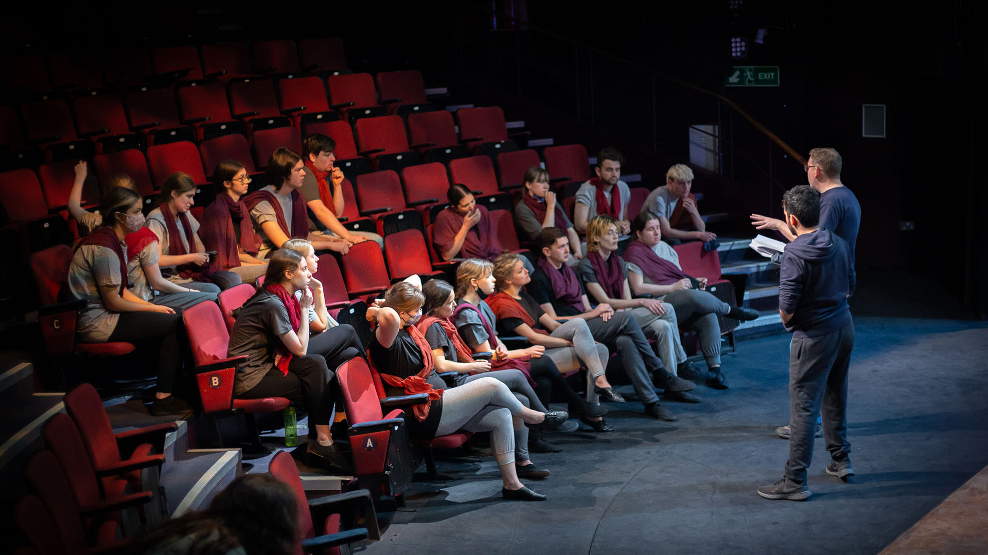 Antigone Rehearsals - the student cast is seated in the auditorium, listening to Director Daniel Buckroyd and Associate Director Yusuf Niazi