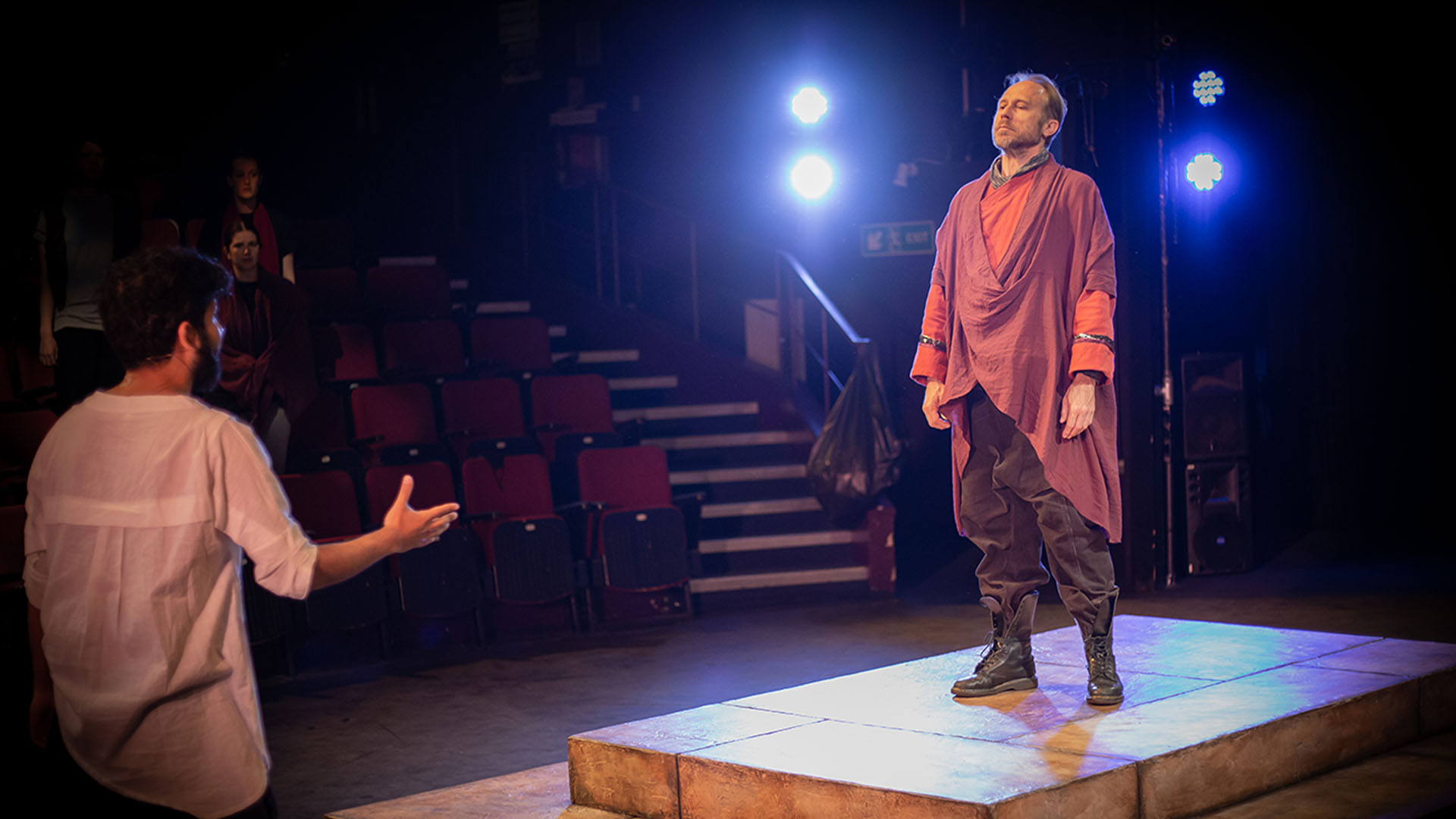 Antigone Rehearsals - David Annen as Kreon on a small platform on stage, wearing a modern toga style costume and combat boots, being directed by Associate Director Yusuf Niazi