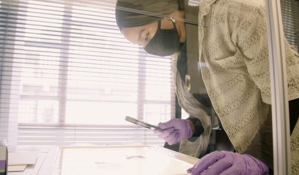 Latifah Wallace looking at archive materials through a magnifying glass