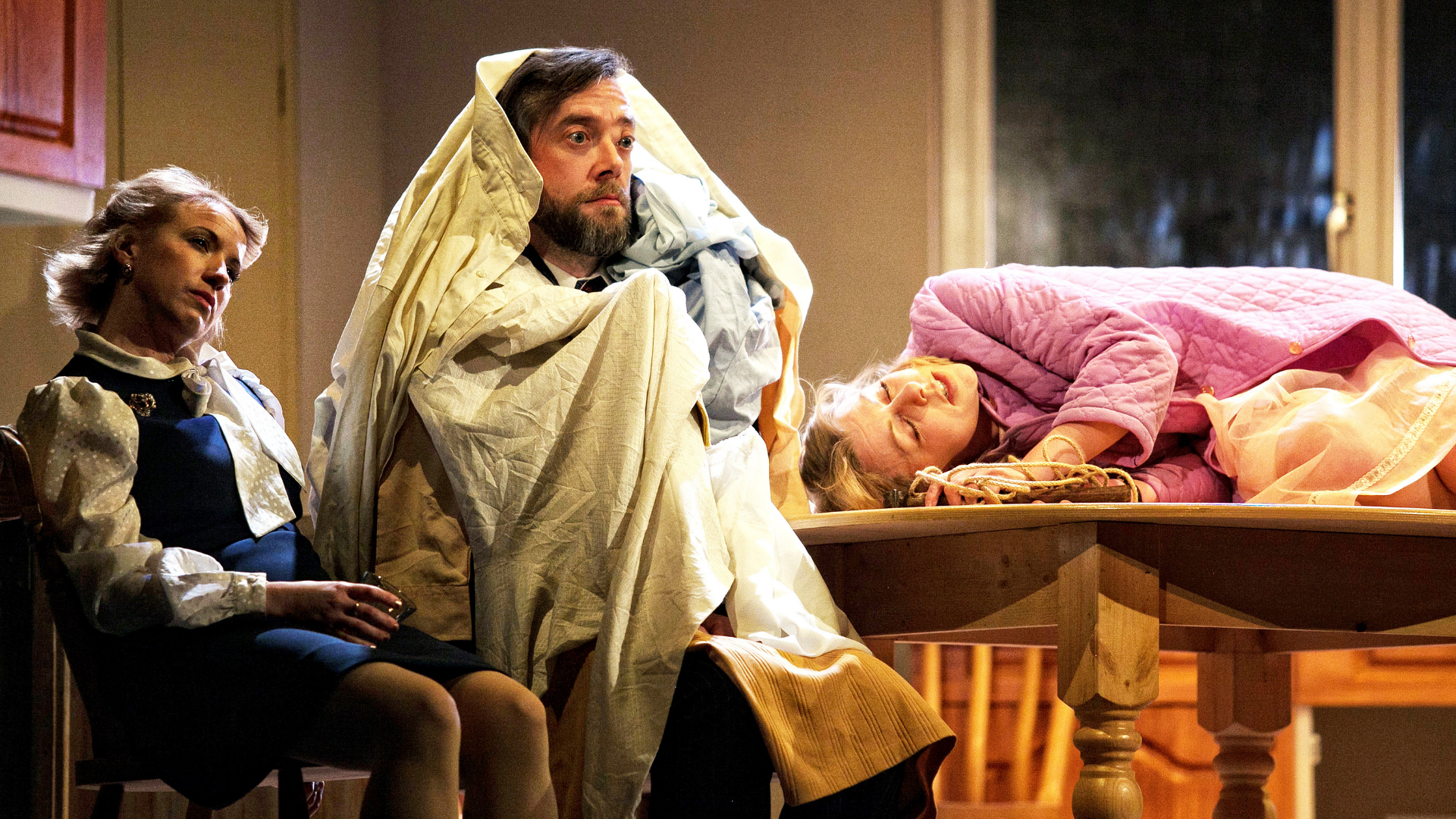 3 characters looking tired and fed up. 1 lady is laid on the kitchen table and another man is under a pile of clothes