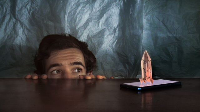 A man peeks out from under a table starring at a rocket made of paper that sits on the table-top