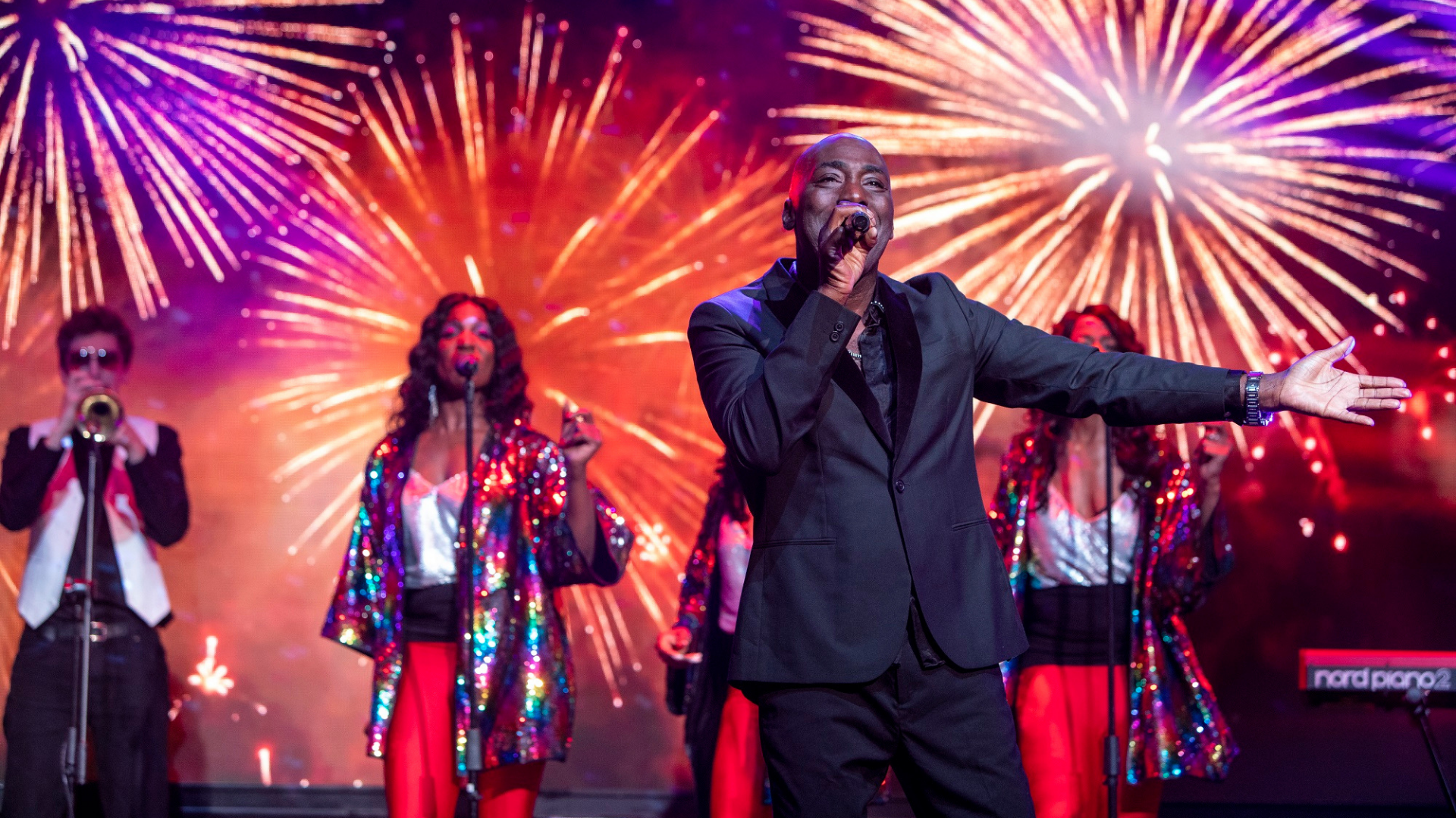 Lost in Music production shot: a male singer wearing a suit sings animatedly in the foreground, while 3 female backing singers dance in the background