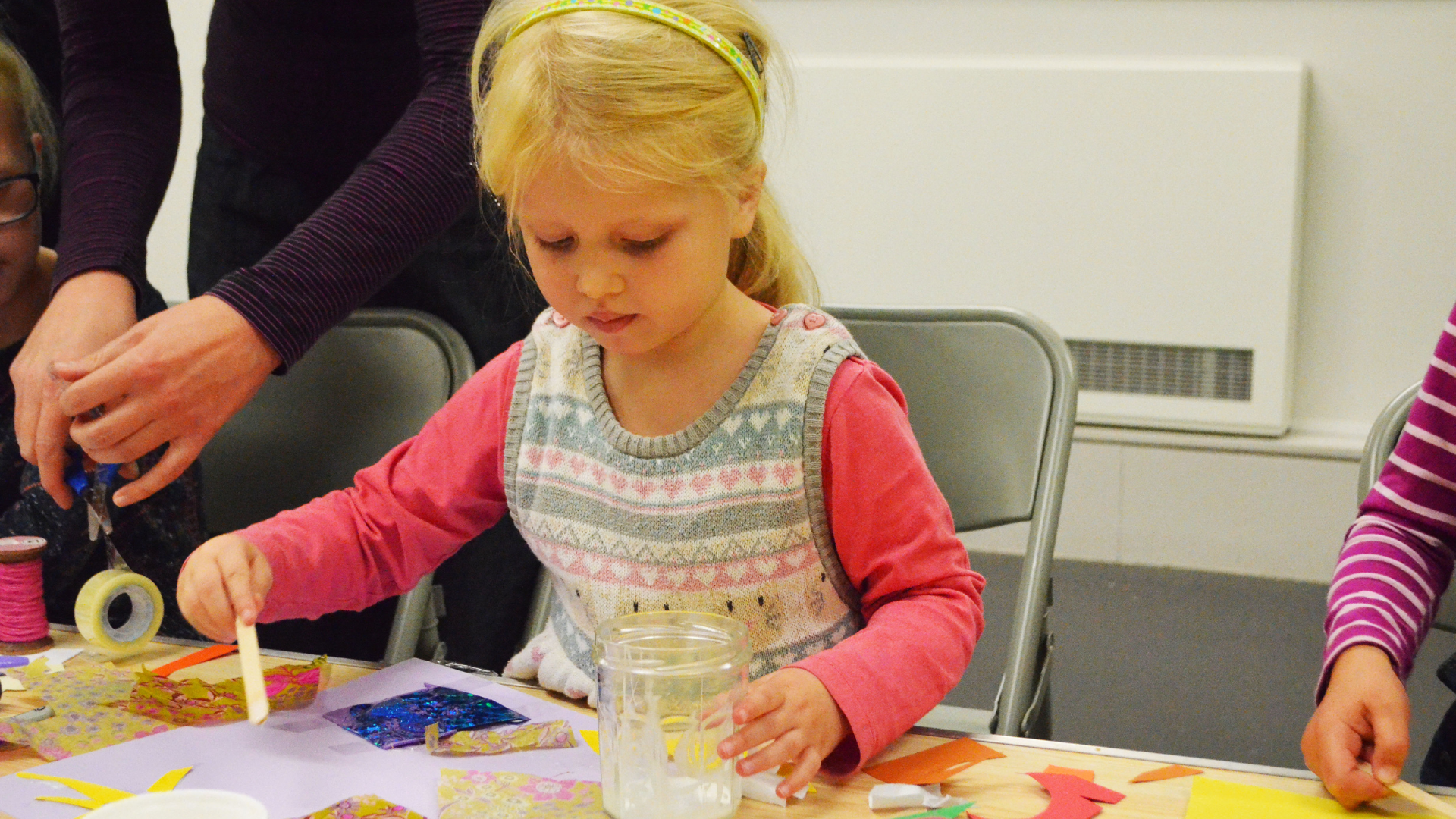 A young blonde girl partakes in craft activities with a look of concentration on her face