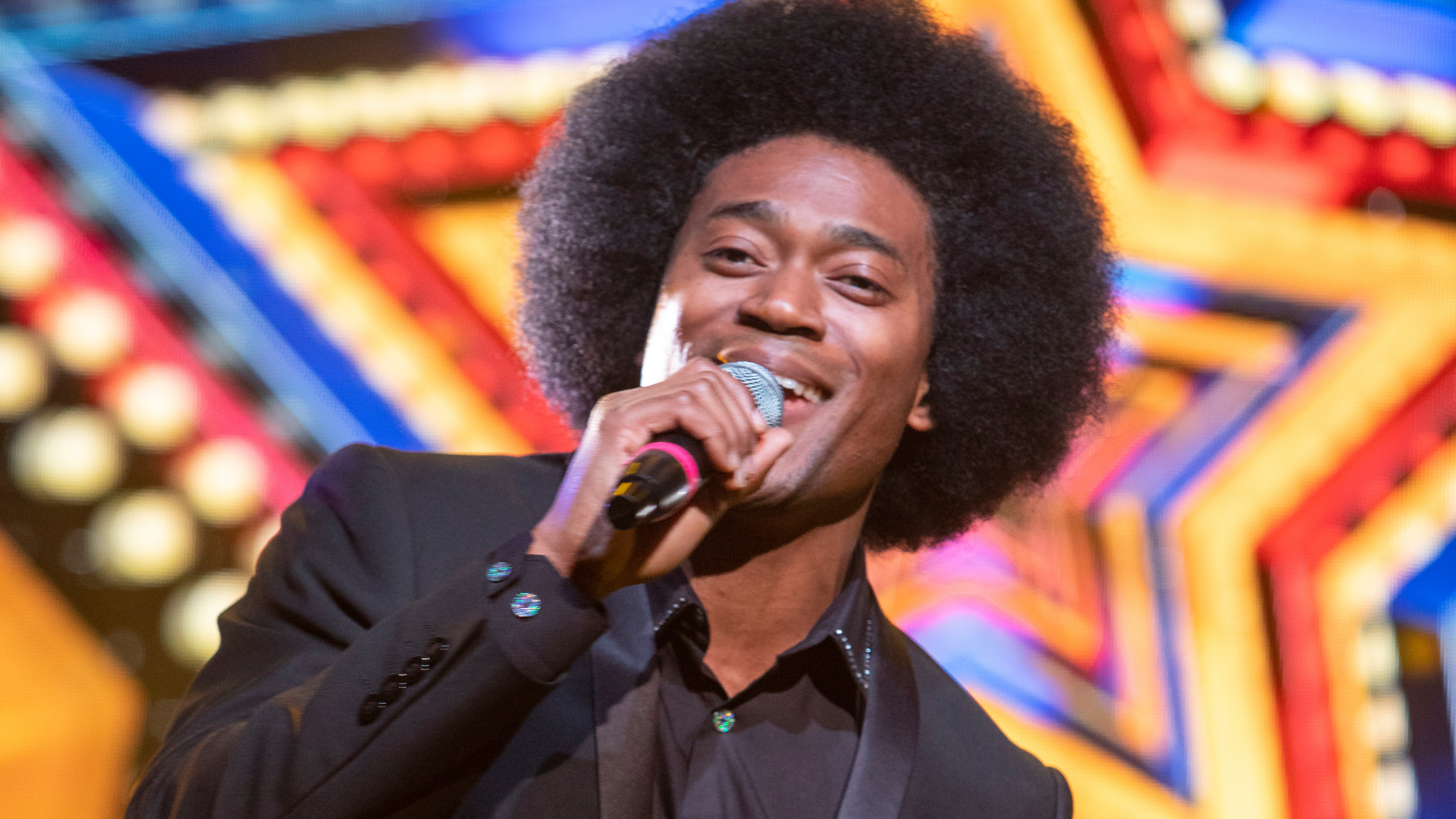 Lost in Music production shot: a close up of one of the male singers, who has a large afro and wear a smart suit