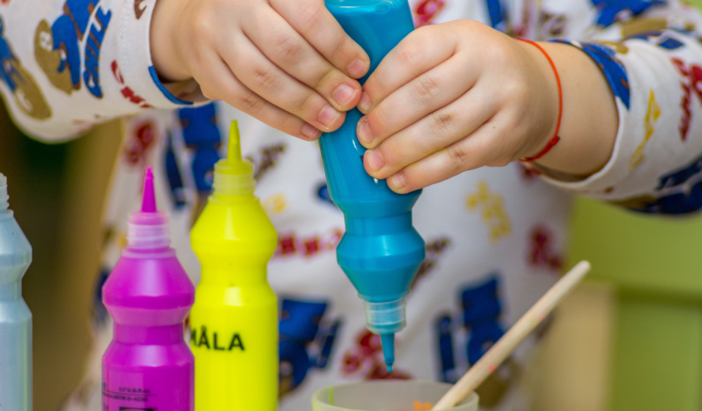 a close up of a young child's hands squeezing paint out of a bottle