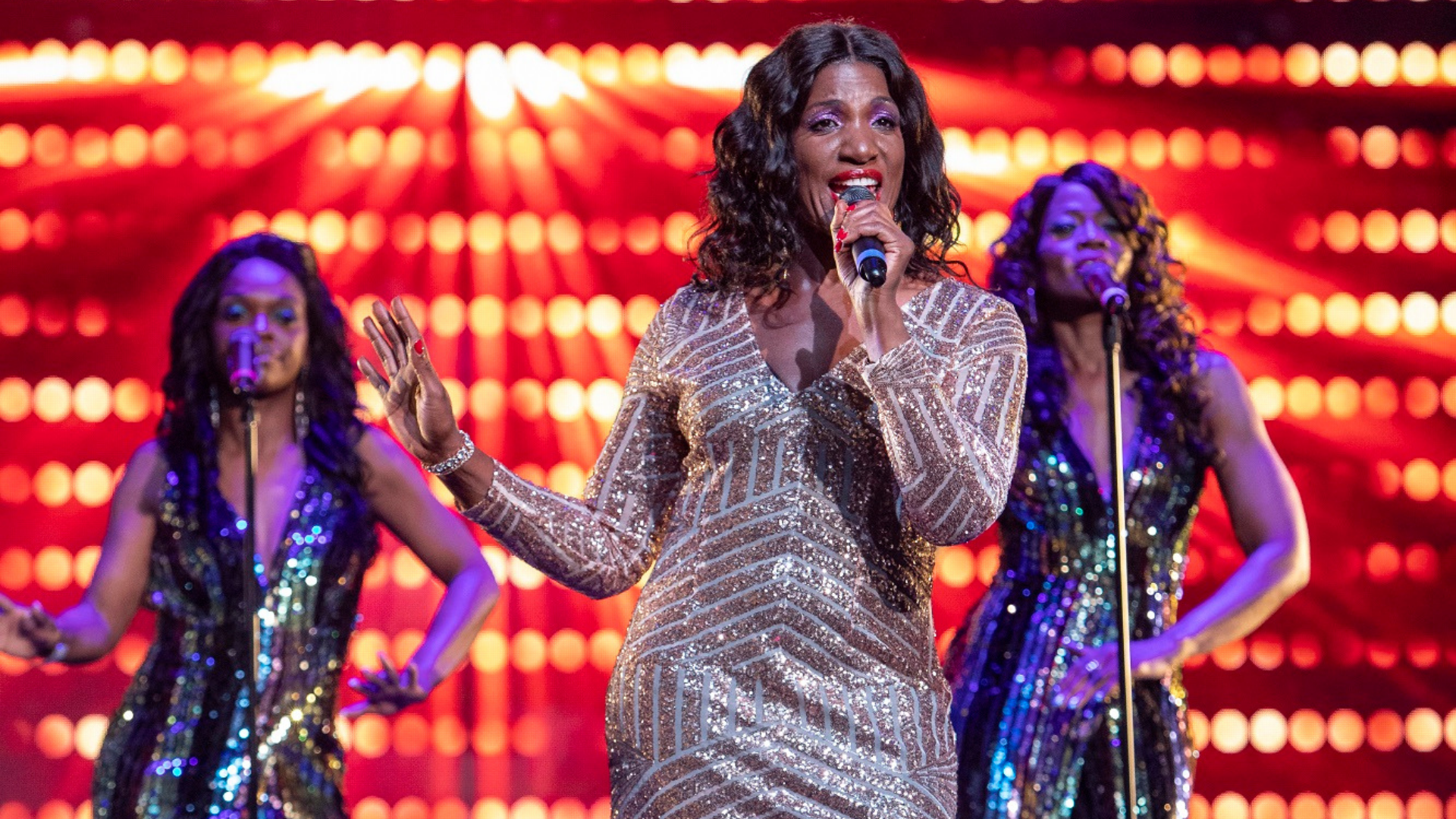Lost in Music production shot: a female singer stands in the foreground wearing a long sequined dress, while two female backing singers dance in the background