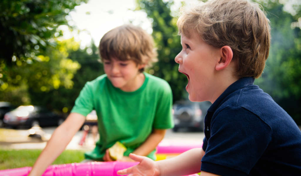 Two male children ages around 5 and 8 play outside. The younger child is laughing